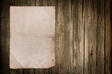 Grungy old paper sheet on wood