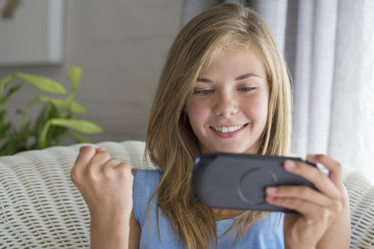 Close-up of a smiling girl playing video game
