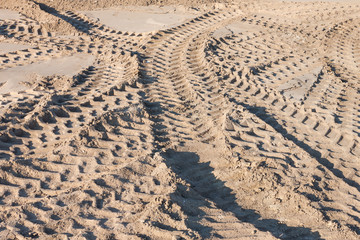 pattern of tractor wheel printed on sand road use as background
