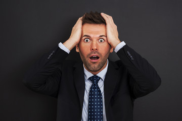 Businessman holding his head and screaming