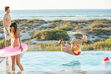 Three friends enjoying at a swimming pool on the beach