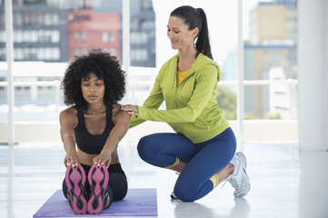 Woman practicing yoga with the help of an instructor