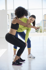 Female instructor assisting a woman in a gym