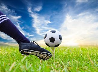 foot kicking soccer ball on golf tee