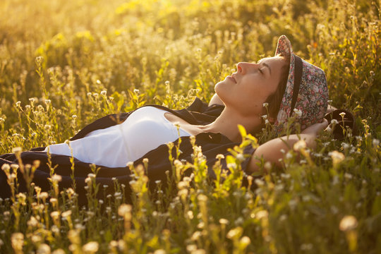 The girl in a hat dremet among wildflowers