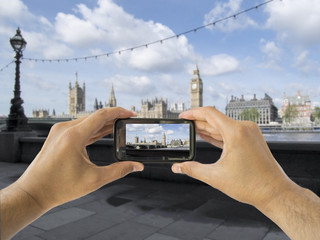 tourist holds up camera mobile at big ben