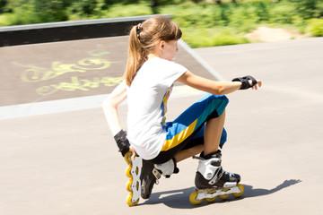 Teenage girl in rollerblades crouching down