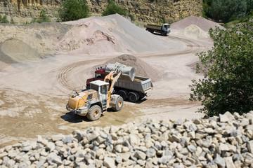 Bagger belädt im Steinbruch LKW