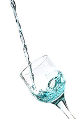 Splash of blue water into the glass