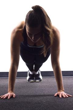 young Caucasian woman doing push ups