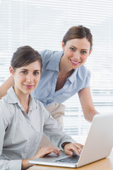 Businesswomen smiling at camera with laptop