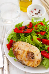 fish with salad on plate and olive oil