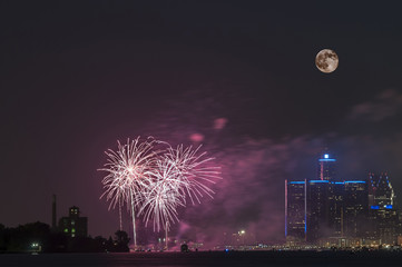Fireworks with full moon over detroit river