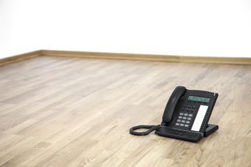 Umzug schwarzes Telefon auf dem Fussboden Büro ohne Möbel