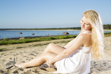 Woman in white dress indulgence on sand