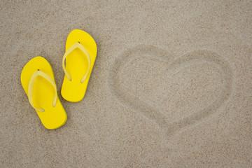 yellow flip flops and heart on sandy beach