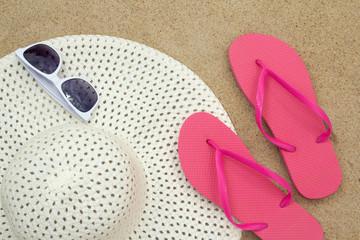 flip flops, sunglasses and hat on sandy beach