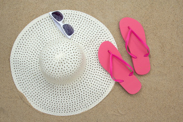 pink flip flops, sunglasses and hat on sandy beach