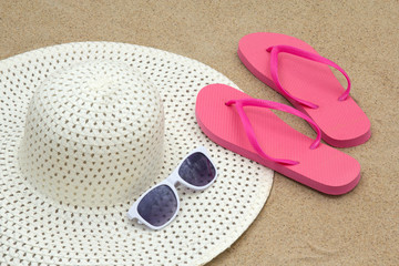 red flip flops, sunglasses and hat on sandy beach