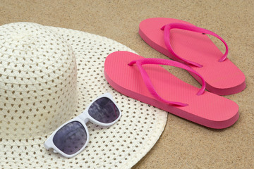 picture of pink flip flops, sunglasses and hat on beach sand