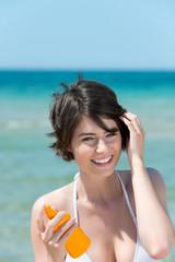 frau mit heller haut benutzt sonnencreme am strand