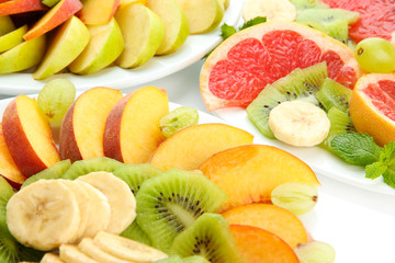 Assortment of sliced fruits on plates, close up