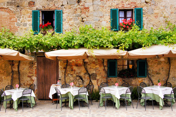 Foto op Canvas Toscane Cafe tables and chairs outside a stone building in Tuscany