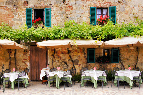 Fotomurales Cafe tables and chairs outside a stone building in Tuscany
