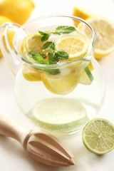 Jug of fresh lemonade with mint leaves and wooden squeezer.