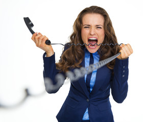 Angry business woman biting phone cord