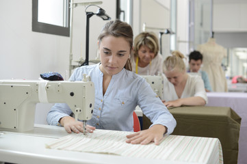 Student girl in training class working on sewing machine
