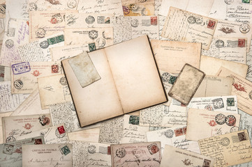 old handwritten postcards and open diary book