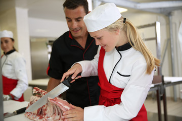 Professional butcher teaching student with meat cutting