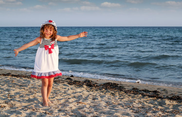 Wall Mural - beautiful happy little girl on beach summer scene