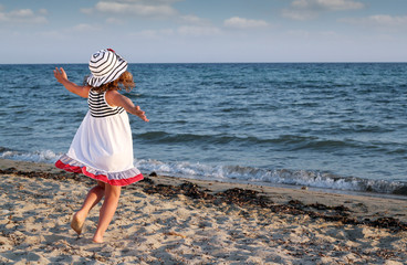 Wall Mural - happy little girl running on beach