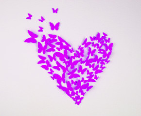 Paper purple butterfly in form of heart on wall