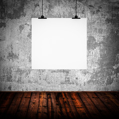 Interior of grunge empty room with white paper hanging on paper