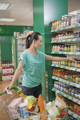 Woman reaching for jar on the shelf in the supermarket, Beijing