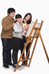 Girl painting with parents