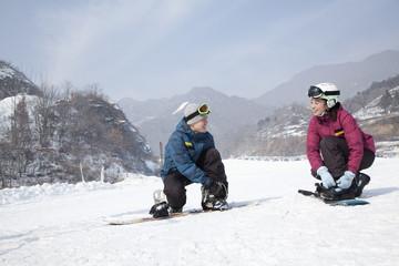 Couple adjusting Ski Boots in Ski Resort