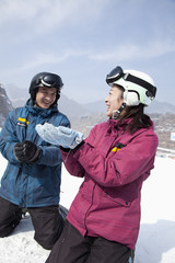 Young Man and Woman Playing in the Snow in Ski Resort