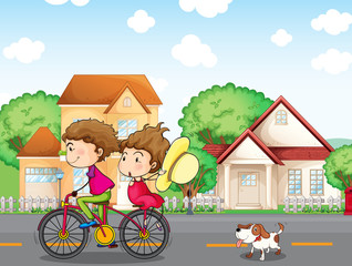 A boy and a girl biking followed by a dog