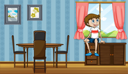 A boy sitting above the cabinet near the window
