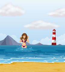 A beach with a lady in a purple bikini