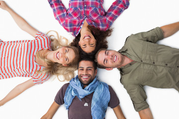 Friends lying in a circle and smiling at camera