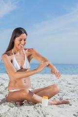 Smiling woman sitting on beach  applying sunscreen