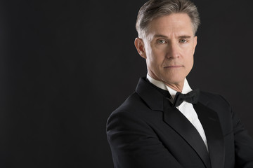 Confident Man In Tuxedo Staring Against Black Background