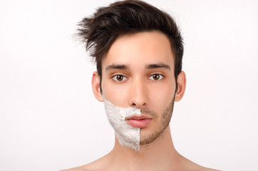 Young man shaving his beard in the morning with a razor