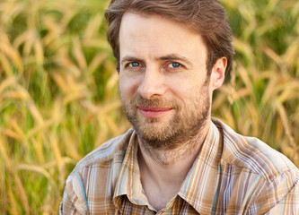 Happy smiling farmer in front of his wheat field