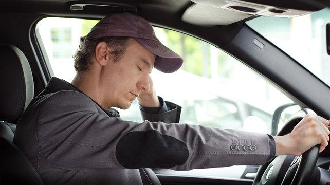 Bored man at the wheel of his car sleeping